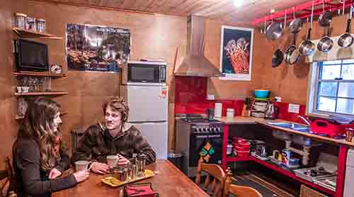 Young couple sitting at the kitchen table in the Settlers Hut